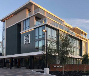 A street view of the front of the AC Hotel by Marriott Palo Alto, a dual-branded hotel designed by hotel architect AXIS/GFA Architecture + Design